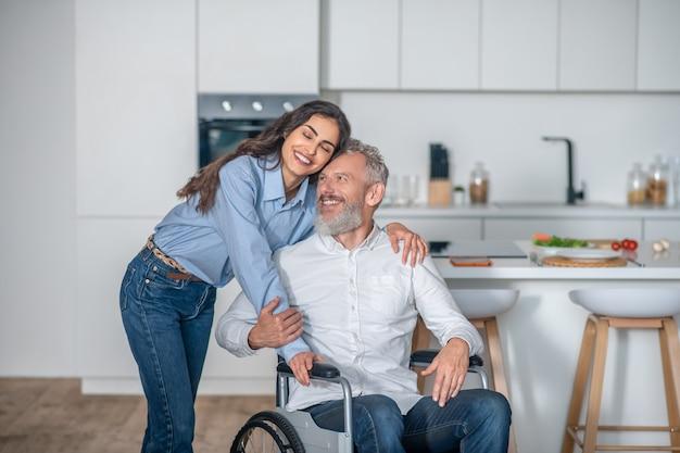 Szczęśliwa para. młoda długowłosa kobieta uśmiecha się ładnie do swojego niepełnosprawnego męża i oboje wyglądają na szczęśliwych