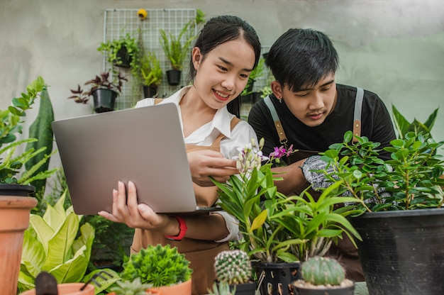 Szczęśliwa para młodych ogrodników z azji w fartuchach korzysta ze sprzętu ogrodowego i laptopa, aby się opiekować