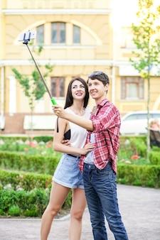 Szczęśliwa para młodych turystów biorąca selfie ze smartfonem na monopod w mieście, w którym jest mężczyzna