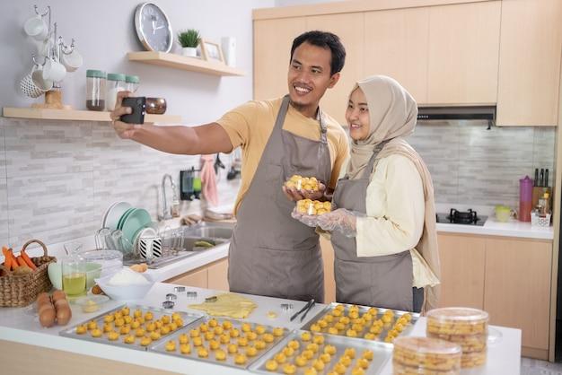 Szczęśliwa para muzułmańska przy selfie z jedzeniem w domu razem w kuchni. eid mubarak celebrowanie gotowania