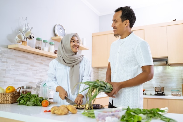 Szczęśliwa para muzułmańskich wspólne gotowanie w kuchni. mężczyzna i kobieta przygotowuje się do obiadu