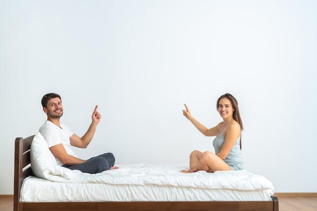 Szczęśliwa para na łóżku gestykuluje na białym tle