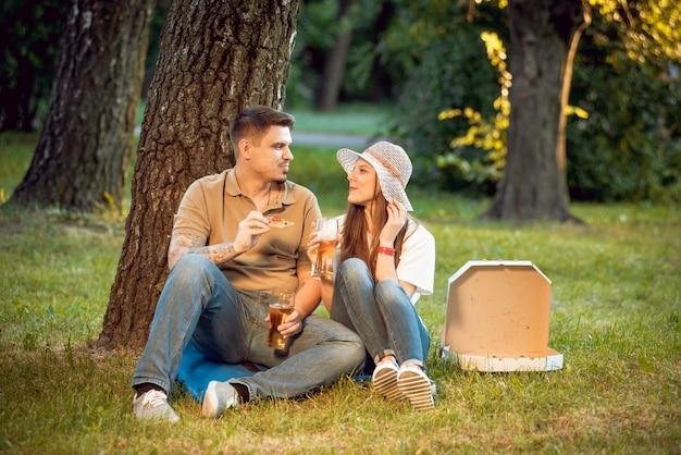 Szczęśliwa para na pikniku w parku. jeść pizzę i pić piwo