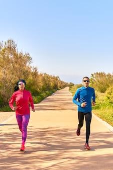 Szczęśliwa para na ścieżce w miły ciepły dzień. kobieta nosi jaskraworóżowe i fioletowe ubrania. mężczyzna ma na sobie niebieską koszulę i czarne długie spodnie.