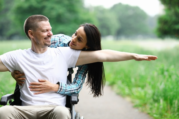 Szczęśliwa para na spacerze w parku niepełnosprawnym wózku inwalidzkim