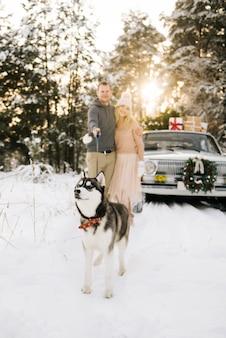 Szczęśliwa para na zimowy dzień z retro samochodów i husky