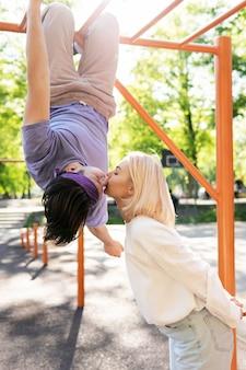 Szczęśliwa para nastolatków bawi się na placu zabaw w parku miejskim
