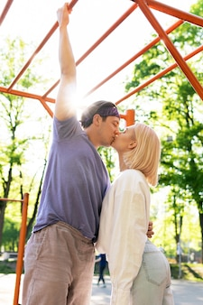 Szczęśliwa para nastolatków całujących się na placu zabaw w parku miejskim
