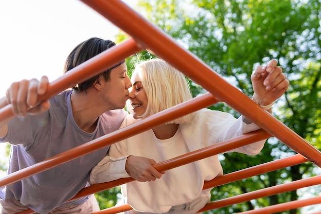 Szczęśliwa para nastolatków na placu zabaw w parku miejskim