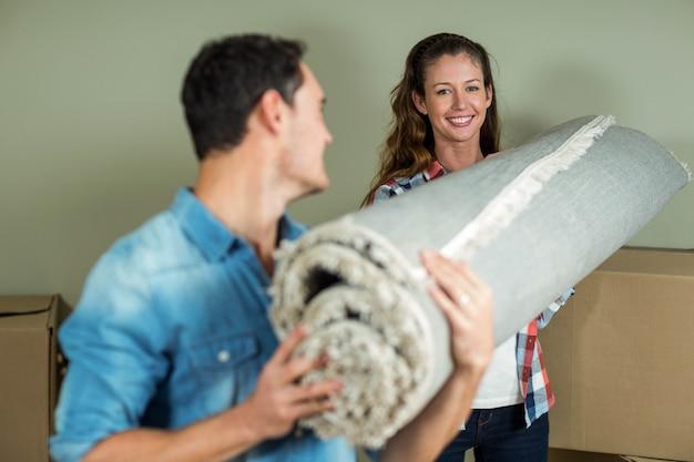 Szczęśliwa para niosąc zwinięty dywan w nowym domu