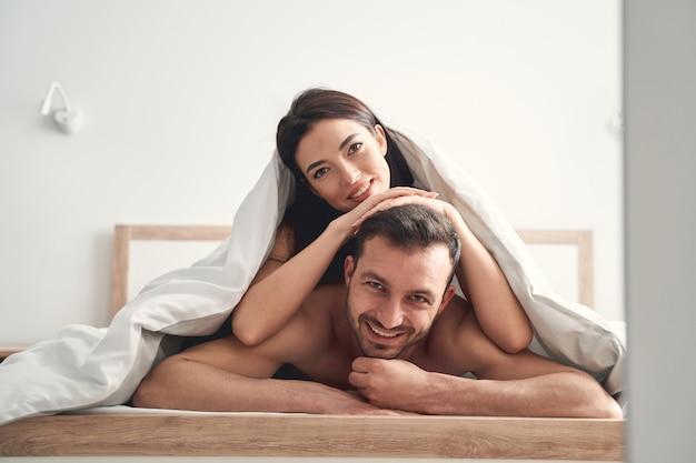 Szczęśliwa para nowożeńców dobrze się bawi w łóżku pod kocem rano