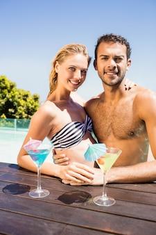 Szczęśliwa para obejmując w basenie z koktajlami na krawędzi basenu