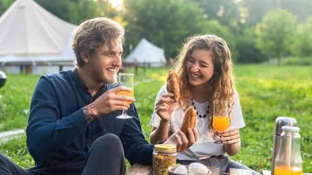Szczęśliwa para odpoczywa na łonie natury w glampingu. napoje i jedzenie, wokół zieleń