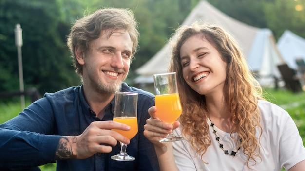 Szczęśliwa para odpoczywa na łonie natury w glampingu. napoje, wokół zieleń
