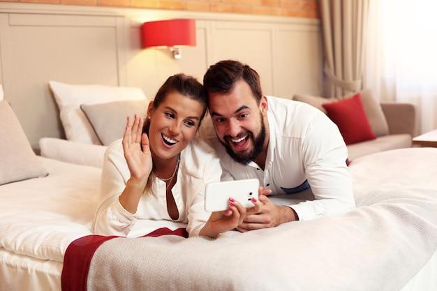 Szczęśliwa para odpoczywa w pokoju hotelowym i korzysta ze smartfona