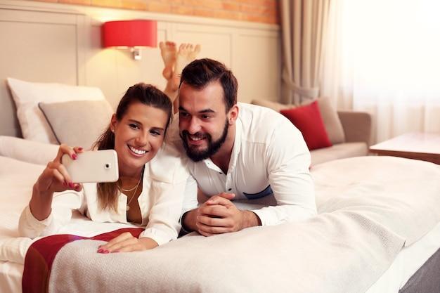 Szczęśliwa para odpoczywa w pokoju hotelowym i robi selfie