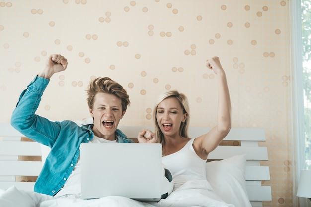 Szczęśliwa para ogląda piłkę nożną na łóżku