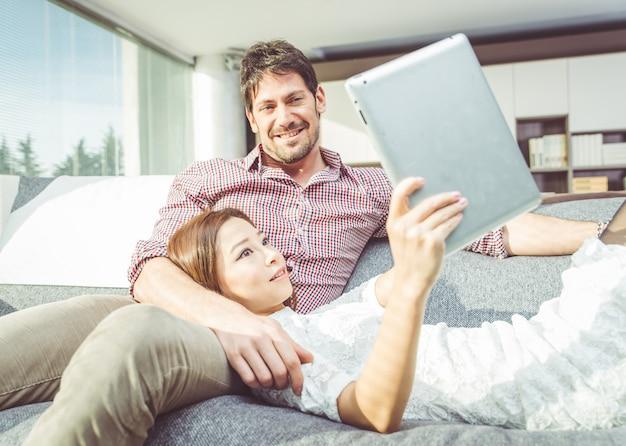 Szczęśliwa para ogląda rzeczy na cyfrowej pastylce w domu w żywym pokoju