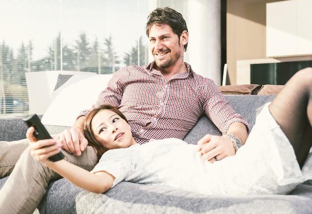 Szczęśliwa para ogląda telewizję w domu w żywym pokoju