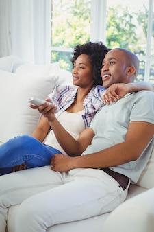 Szczęśliwa para ogląda tv na kanapie