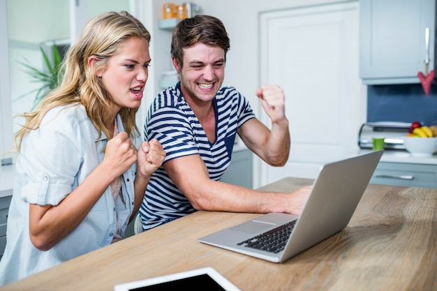 Szczęśliwa para oglądania filmów na laptopie w kuchni