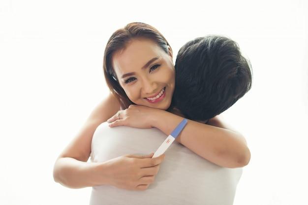 Szczęśliwa para ono uśmiecha się po znajduje out pozytywnego ciążowego test w sypialni