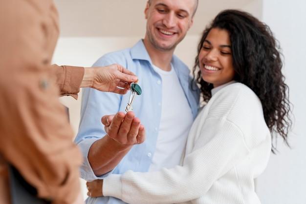 Szczęśliwa para otrzymująca klucze do swojego nowego domu od pośrednika w handlu nieruchomościami