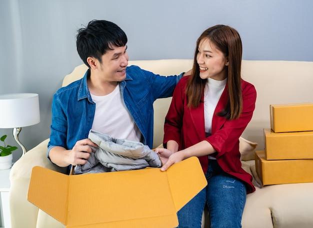 Szczęśliwa para otwiera kartonową paczkę w salonie w domu, kup w sklepie internetowym