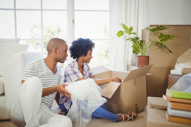 Szczęśliwa para otwiera pudełka w żywym pokoju