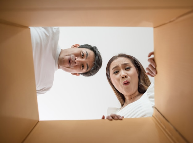 Szczęśliwa para otwiera pudełko i patrzeje inside produkt