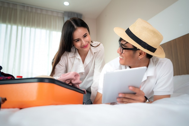 Szczęśliwa para pakuje walizkę na łóżku w sypialni, leżącej i przyglądającej cyfrowej pastylce dla rewizi podróży wycieczki online. azjatycki backpacker podróży styl życia koncepcji.