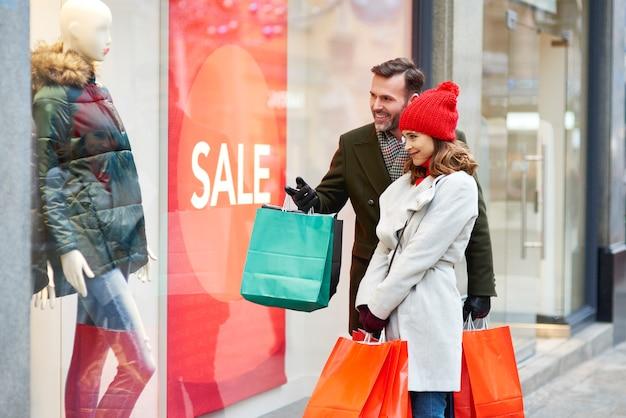 Szczęśliwa para patrząc na duży wyświetlacz w sklepie