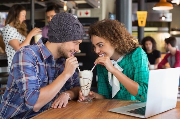 Szczęśliwa para patrząc na siebie mając koktajl mleczny