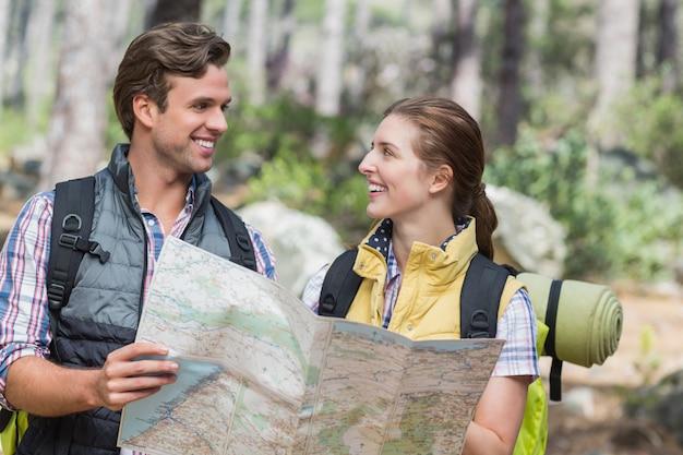 Szczęśliwa para patrzeje twarz w twarz podczas gdy trzymający mapę