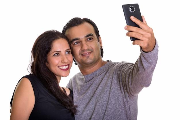 Szczęśliwa para perski uśmiechnięty podczas robienia zdjęcia selfie