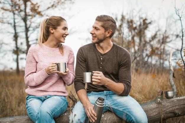 Szczęśliwa para picia gorącego napoju na postoju na zewnątrz