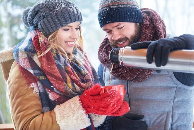 Szczęśliwa para picia gorącej herbaty w zimie