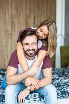 Szczęśliwa para. piękna młoda para zabawy w sypialni w domu, podczas gdy mężczyzna bez koszuli daje swojej dziewczynie przejażdżkę na świnkę