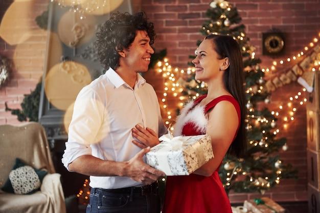 Szczęśliwa para piękny z okazji nowego roku w ozdobnym pokoju. facet z kręconymi włosami daje dziewczynie prezent na boże narodzenie.