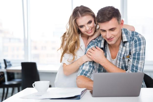 Szczęśliwa para pijąca kawę i używająca laptopa razem