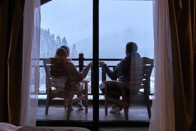 Szczęśliwa para pije kawę na balkonie górskiego hotelu z pięknym widokiem na góry
