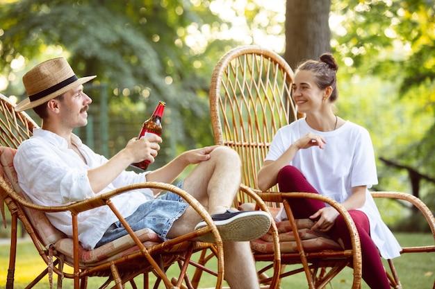 Szczęśliwa para pije piwo na kolację z grilla na zachód słońca. wspólny posiłek na świeżym powietrzu na leśnej polanie. świętowanie i relaks, wyglądaj na szczęśliwego. letni styl życia, jedzenie, rodzina, koncepcja relacji.