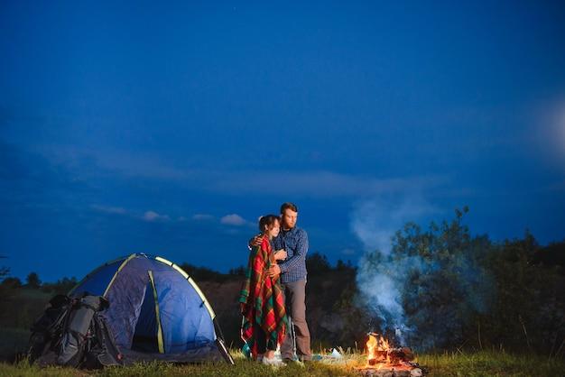 Szczęśliwa para podróżnych siedzi razem przy ognisku i świecącym namiocie turystycznym