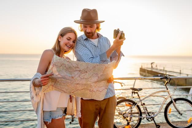 Szczęśliwa para podróżująca latem na rowerach, patrząc na mapę i robienie zdjęć w aparacie