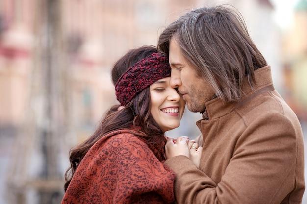 Szczęśliwa para pozuje na starym kwadracie miasto. całkiem piękna kobieta i jej przystojny stylowy mężczyzna przytulanie na ulicy. czas jesieni lub zimy. zamknij obraz