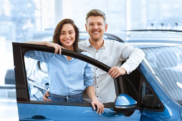 Szczęśliwa para pozuje razem za otwartymi drzwiami nowego samochodu, który właśnie kupili w salonie
