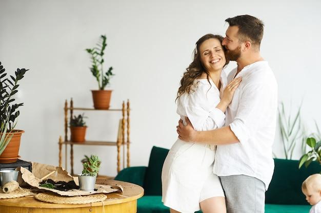 Szczęśliwa para przesadza rośliny w domu.
