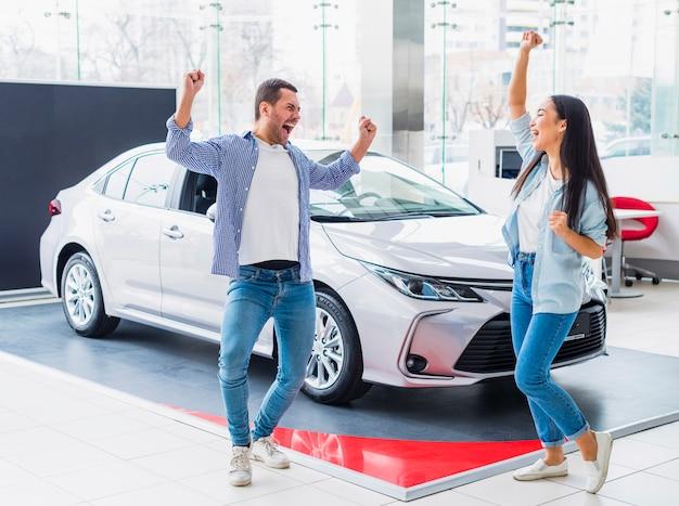 Szczęśliwa para przy przedstawicielstwem handlowym samochodu