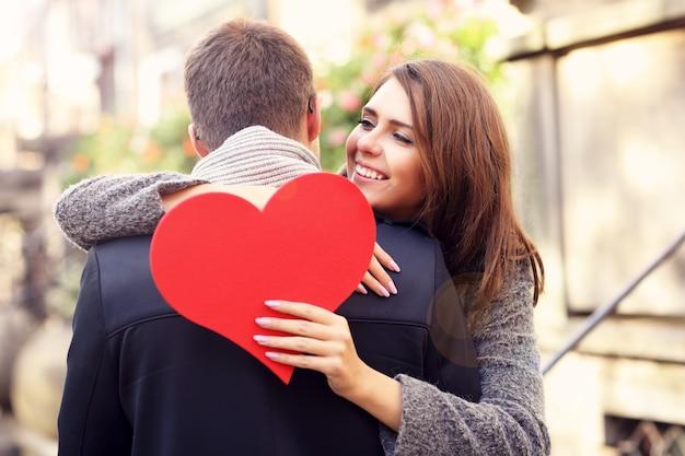 Szczęśliwa para przytulająca się sercem w mieście
