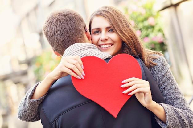 Szczęśliwa para przytulająca się z kwiatami i sercem w mieście